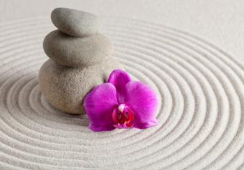 Orchidee, stapelstenen en zand fotobehang